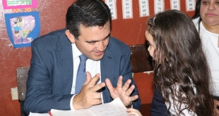 Eduardo Petta, ministro de Educación, en estilo populista, se sienta a enseñar a una pequeña alumna.
