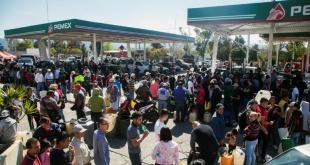 Cientos de personas forman filas para comprar combustible en una estación de gasolina de Morelia, México.