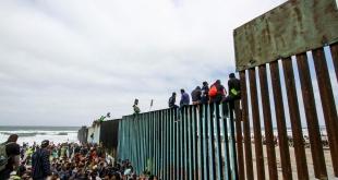 Varios migrantes se aventuran a trepar el muro en la frontera entre México y Estados Unidos.