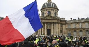 """Un manifestante de los """"chalecos amarillos"""" ondea una bandera francesa durante una manifestación en Le Pont des Arts."""