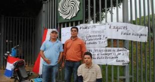 Imágenes Los desvinculados están frente al portón de acceso de la EBY. / Miguel Rodríguez, ABC Color.